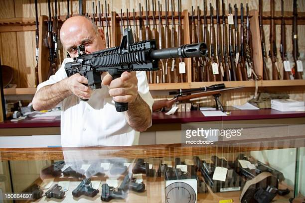 mature merchant aiming with rifle in gun shop - vuurwapen stockfoto's en -beelden