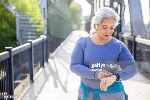 mature mexican woman using fitness tracker - fitness tracker stock pictures, royalty-free photos & images