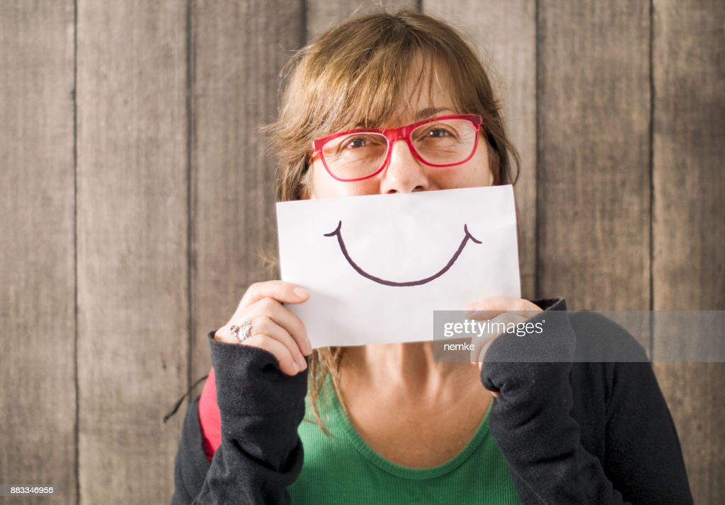 Mature mid age woman with a smile painted on paper : Stock Photo