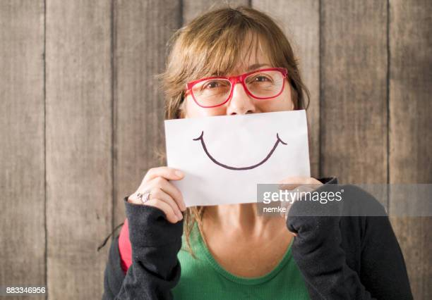 mature mid age woman with a smile painted on paper - smiley face stock pictures, royalty-free photos & images