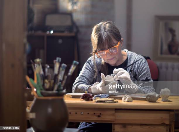 Mature middle aged hobby artist moulding raw clay in art studio