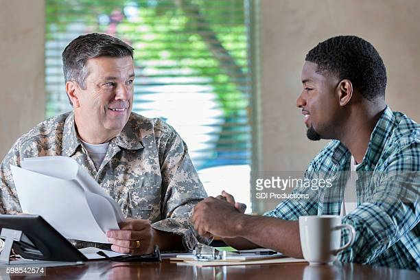 Mature military officer discussing armed forces with new recruit