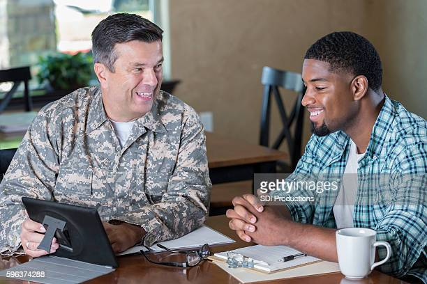 Mature military officer talking to man in recruitment office