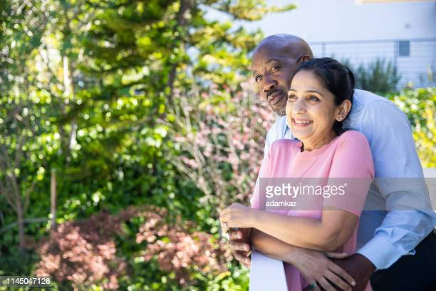 mature mixed race couple relaxing after work - 50 59 years stock pictures, royalty-free photos & images