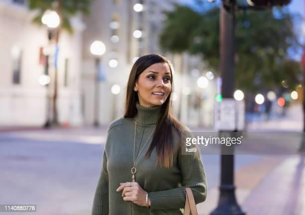volwassen mixed race hispanic vrouw wandelen in de stad - steil haar stockfoto's en -beelden