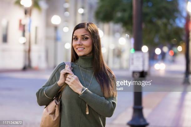 mature mixed race hispanic woman walking in the city - straight hair stock pictures, royalty-free photos & images