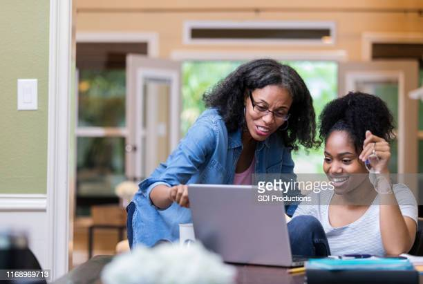 mature mom helps her daughter study - adult offspring stock pictures, royalty-free photos & images