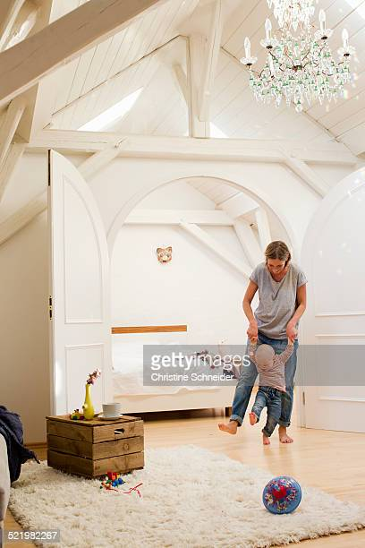 Mature mother and baby daughter walking together in sitting room