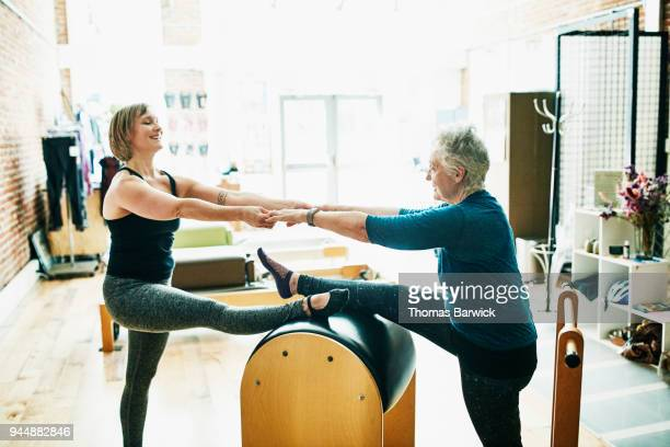 Mature mother and daughter practicing pilates ladder barrel partner stretch together in fitness studio