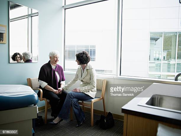 mature mother and daughter sitting in exam room - newhealth stock pictures, royalty-free photos & images