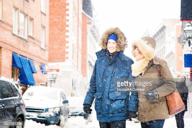 mature mother and her adult son visiting old montreal during a snow storm - vieux montréal stock pictures, royalty-free photos & images