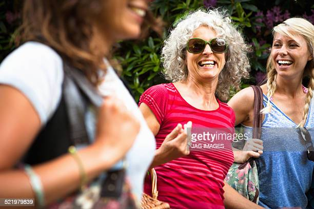 Mature mother and two daughters laughing and chatting whilst walking