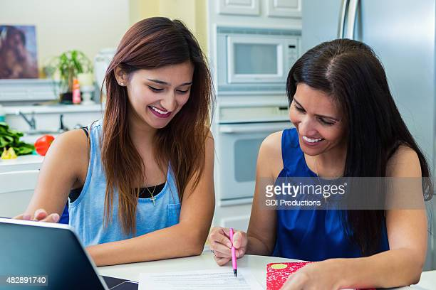 mature mother helping daughter fill out college application - college application stock photos and pictures