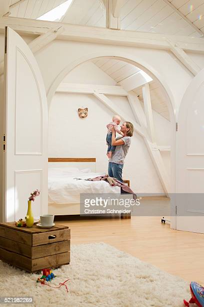 Mature mother holding up baby daughter in bedroom