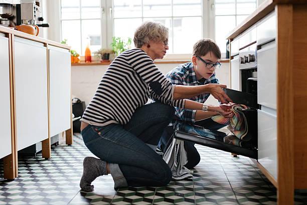 mature mother teaching her teenage son how to bake - 焗 預備食物 個照片及圖片檔