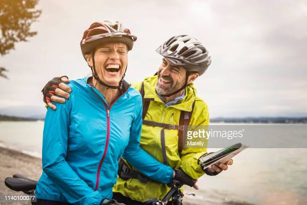 mature mountain biking couple laughing whilst checking map at lakeside - mature couple stock pictures, royalty-free photos & images