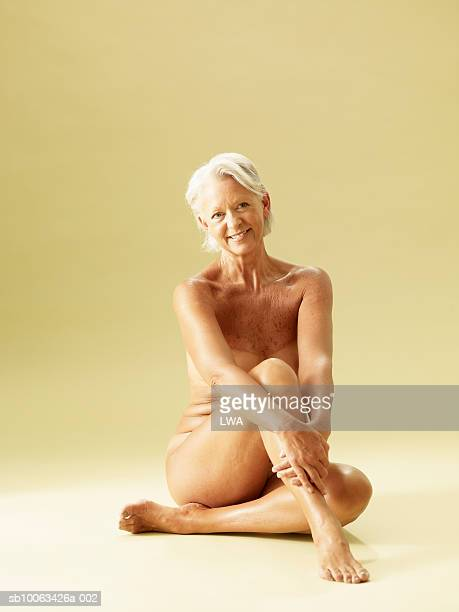 Mature naked woman sitting on floor, smiling, portrait