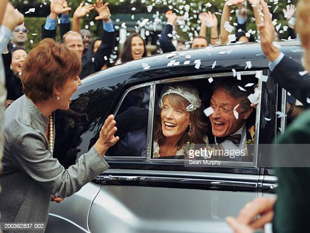 Mature newlywed couple looking out of car window, guests cheering