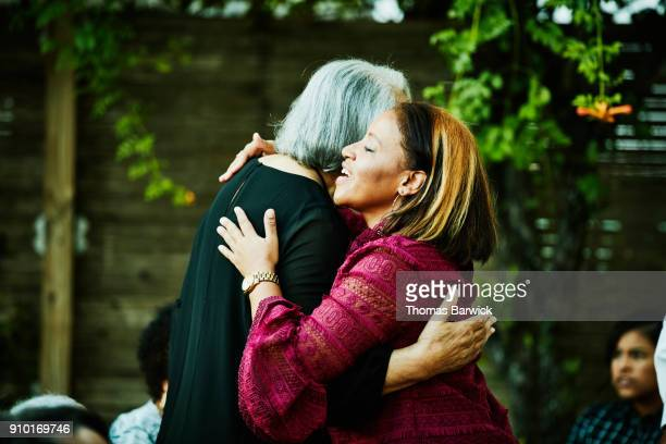 mature niece hugging senior aunt before outdoor dinner party with family - aunt stock pictures, royalty-free photos & images