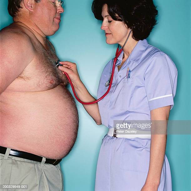 mature nurse listening to man's heart with stethoscope - homme gros ventre photos et images de collection