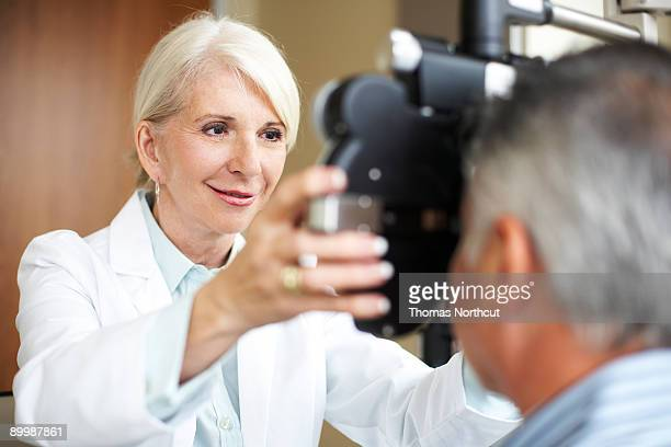 mature opthamologist checks a mature man's vision - optometry stock pictures, royalty-free photos & images