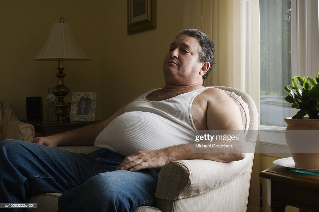 Mature overweight man sitting in armchair : Stock Photo