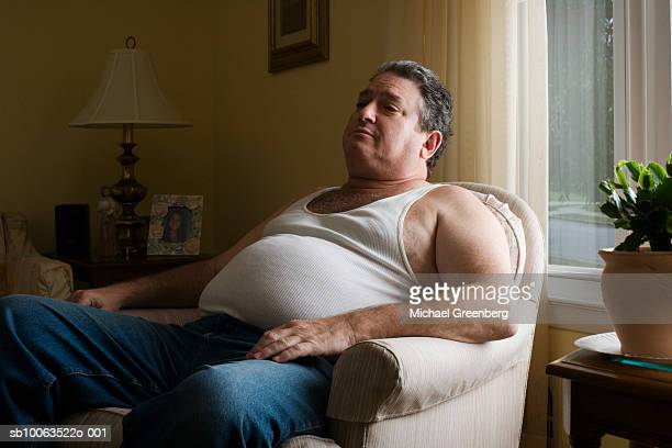 mature overweight man sitting in armchair - chubby men stock photos and pictures