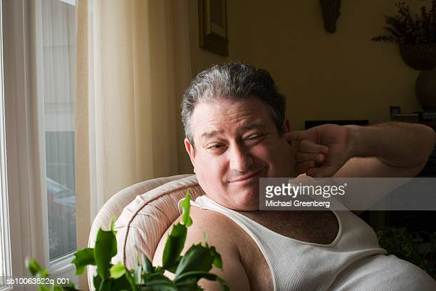 mature overweight man sitting with finger in ear - fingers in ears stock pictures, royalty-free photos & images