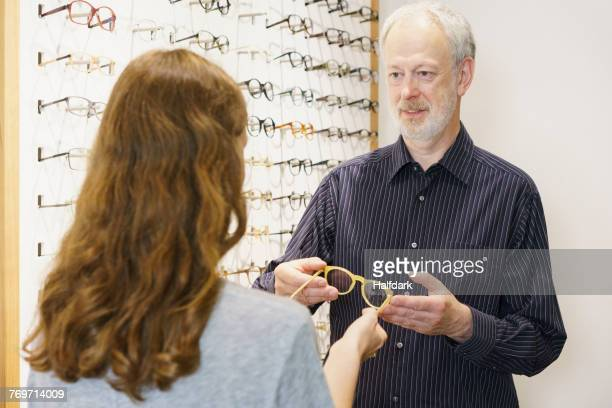 Mature owner showing eyeglasses to woman with brown hair at store