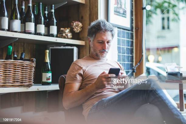 mature owner using smart phone while sitting on chair in deli - 40 44 jahre stock-fotos und bilder