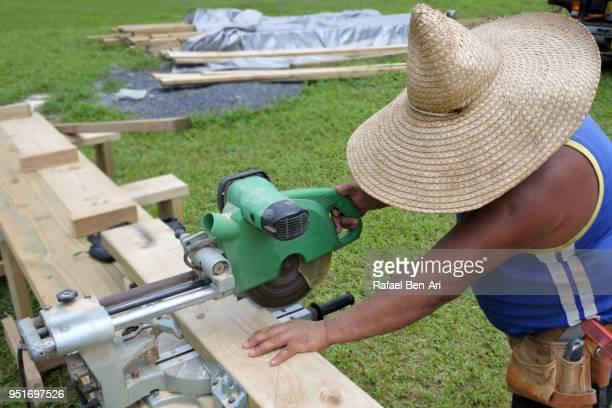 mature pacific islander man cuts plank of wood - rafael ben ari photos et images de collection