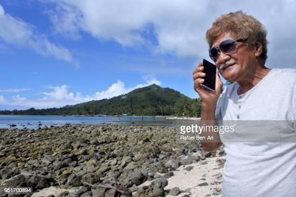 mature pacific islanders man talks on mobile phone - rafael ben ari fotografías e imágenes de stock