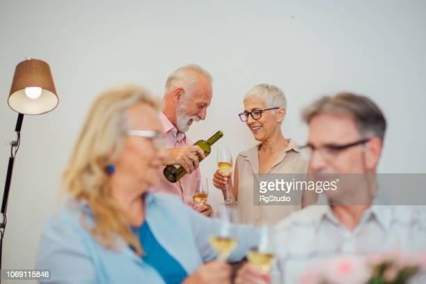 Mature people drinking wine