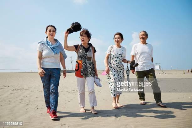 mature people on sunny beach - makiko tanigawa ストックフォトと画像