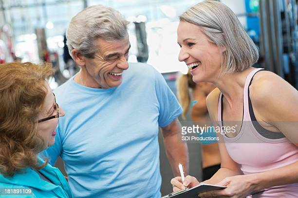 Mature personal trainer giving seniors tour of fitness gym