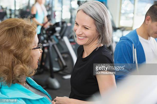 Mature personal trainer training senior client in fitness gym