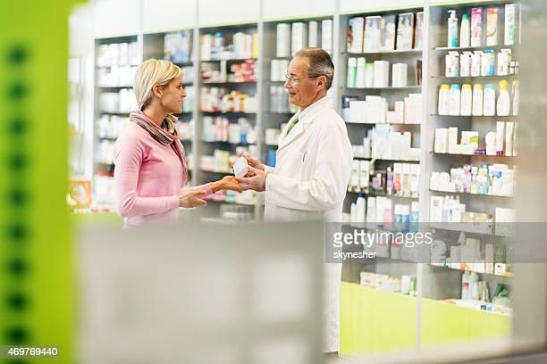 Ältere Apothekerberuf unterstützt junge Frau in der Apotheke.