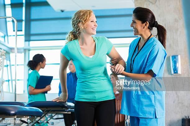 Mature physical therapist helping injured teenage girl to walk