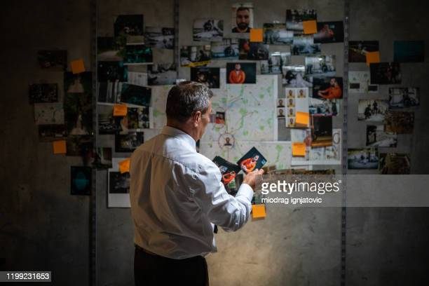 mature police detective looking at pictures while standing in front of the wall - exploration stock pictures, royalty-free photos & images