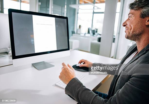 Mature Professional Businessman typing on keyboard in office