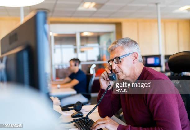 maturité professionnelle parler au téléphone au bureau - hommes d'âge moyen photos et images de collection