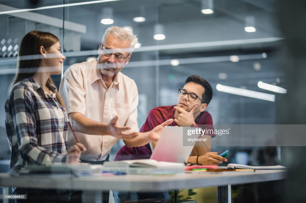 Mature professor explaining the lecture to his students while using laptop at campus. : Stock Photo