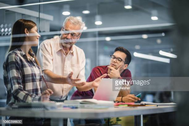mature professor explaining the lecture to his students while using laptop at campus. - academy stock pictures, royalty-free photos & images