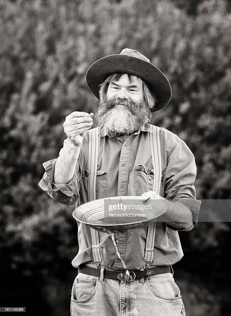 Mature prospector panning for gold vertical : Stock Photo