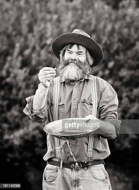mature prospector panning for gold vertical - gold rush stock photos and pictures
