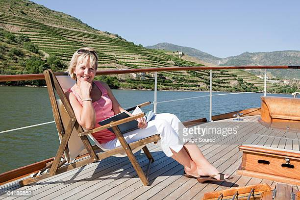 mature reading book woman on a boat holiday - douro valley stock photos and pictures