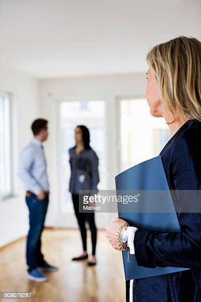 Mature real estate agent looking at couple discussing at home