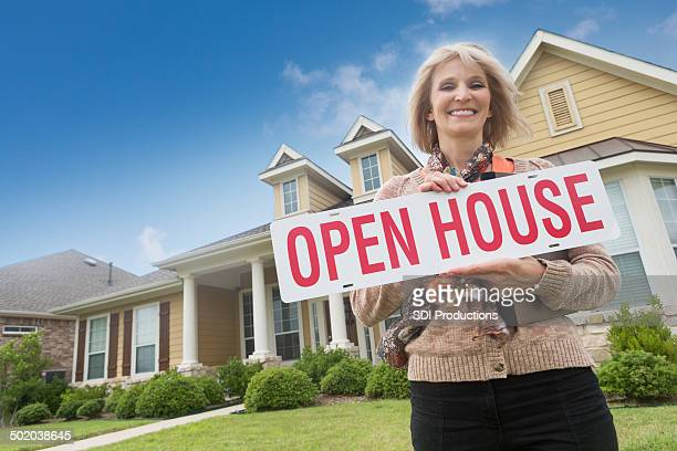 Mature realtor holding open house'' sign in front yard