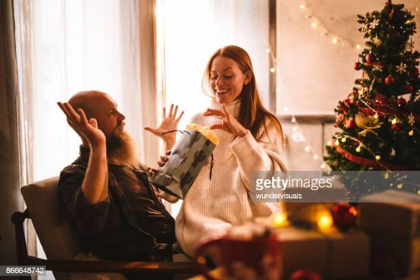 volwassen roodharige paar geven van kerstmis geschenken op eerste kerstdag - vriendje stockfoto's en -beelden