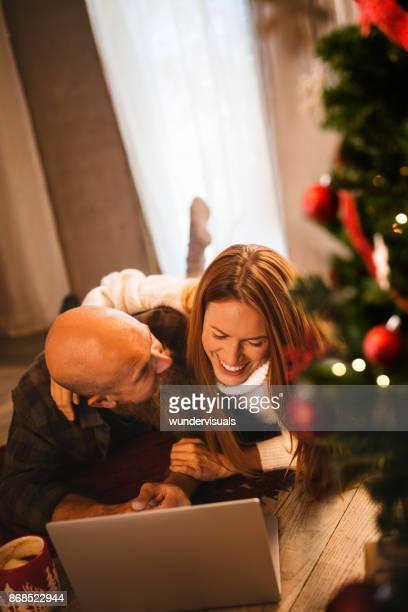 Mature couple rousse s'amusant à l'aide d'ordinateur portable sous le sapin de Noël